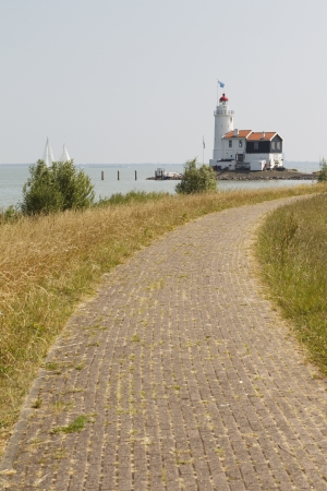 Landscape photo showing a dyke leading up to a beautiful old lighthouse  Stock Photo