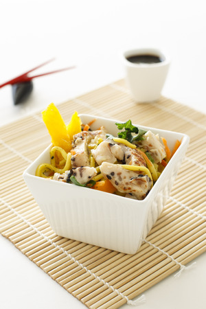 A sesame chicken noodle salad with chopsticks and soy sauce