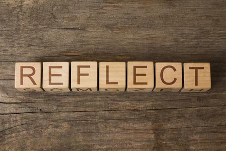 REFLEKTIEREN Wort auf einem hölzernen Würfel