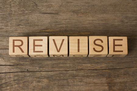 revise: the word of REVISE on a wooden cubes