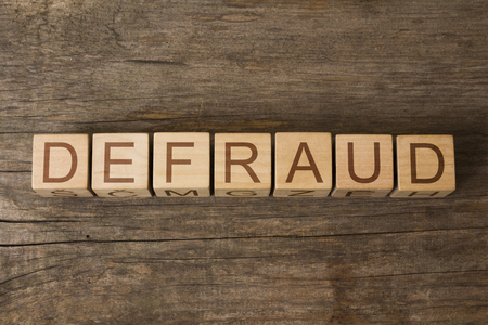 hoax: the word of DEFRAUD on a wooden cubes