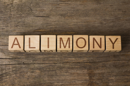 alimony: the word of ALIMONY on wooden cubes Stock Photo