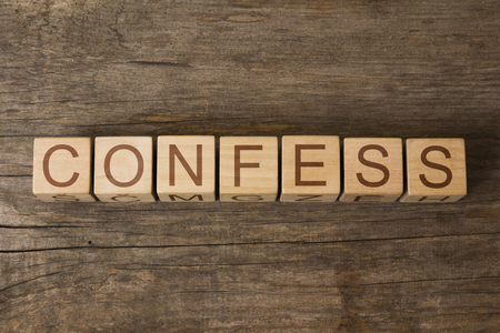 disclose: the word of CONFESS on a wooden cubes