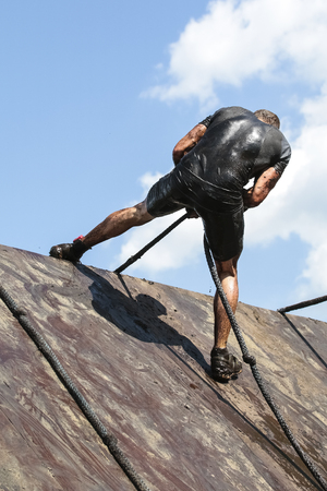 Muddy obstacle race runner in action. Mud run. Stock Photo