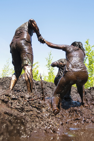 Muddy obstacle race runners in action. Mud run. Stock Photo