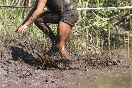 Muddy obstacle race runner in action. Mud run. Stok Fotoğraf