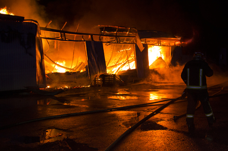 a garage on fire with flames coming thought the roof Reklamní fotografie