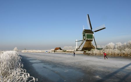 traditionally dutch: Skaters on the ice at Kinderdijk, The Netherlands. Several windmills visible against a clear blue sky.