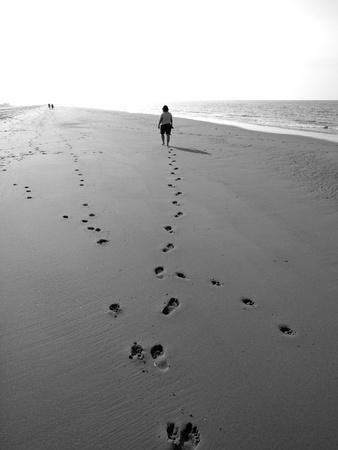 adult footprint: female walking on the beach towards the lightht