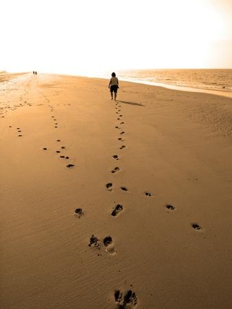 Woman walking on the beach towards the light Stock Photo - 9034677