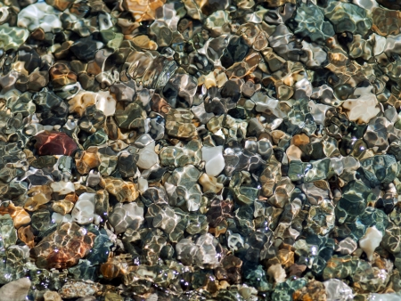 clear: Crystal clear wave lapping over multi colored pebbles