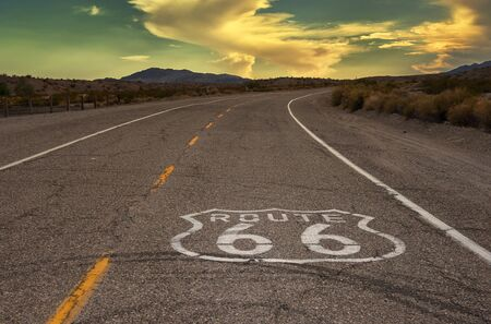 Empty route 66 in California, USA at sunset with marker on road