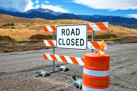 Road closed sign with cone on dirt road