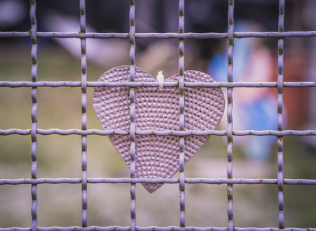 tinkered: Tinkered and self made heart hanging behind a grid fence