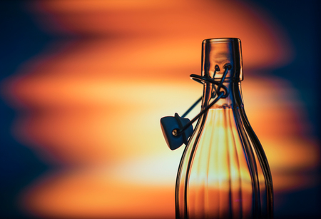 Open glass bottle in front of a creative background