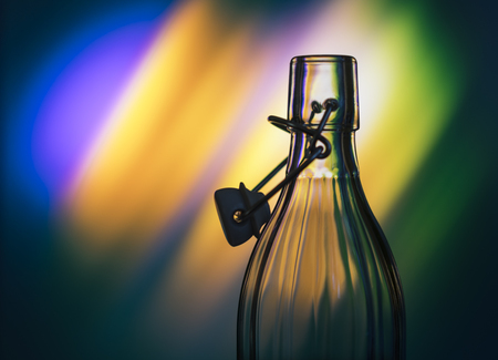 colored bottle: Open glass bottle in front of a creative background