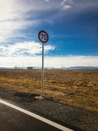 Speed limit sign in front of a field
