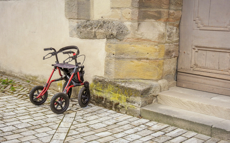 Single wheeled walker or rollator parked in front of the church entrance