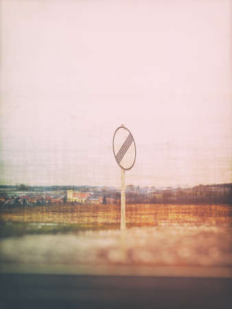 White traffic sign on a blurry landscape background with grunge effects