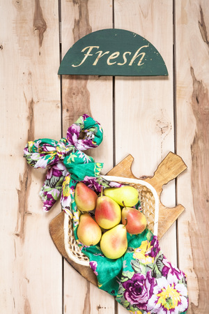 backround: Organic seasonal pear in the basket on the wooden backround with colorful napkin