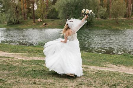 Wedding on the river bank. Happy bride Фото со стока