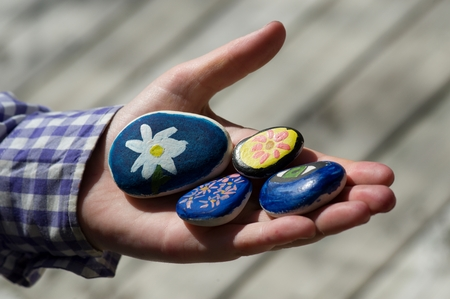 Close-up of a person's hand holding painted stones Stock fotó