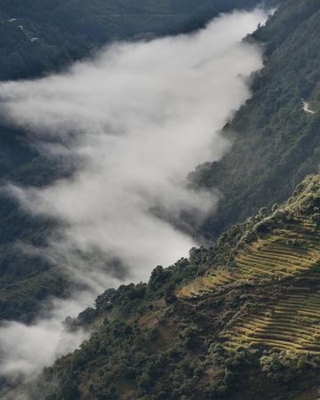 High angle view of a foggy valley, Trongsa District, Bhutan Banco de Imagens - 97736651