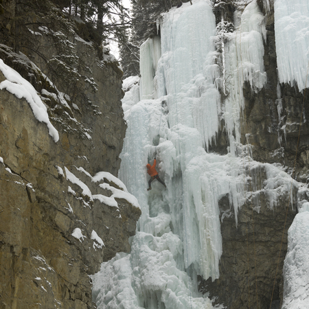 Ice climber on frozen waterfall, Johnston Canyon, Banff National Park, Alberta, Canada
