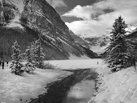 Stream flowing in snow covered valley in winter, Lake Louise, Banff National Park, Alberta, Canada