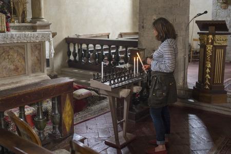 Woman igniting candles in church, Chianti, Tuscany, Italy 免版税图像