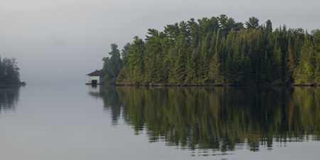 Reflection of trees on water, Lake of The Woods, Ontario, Canada