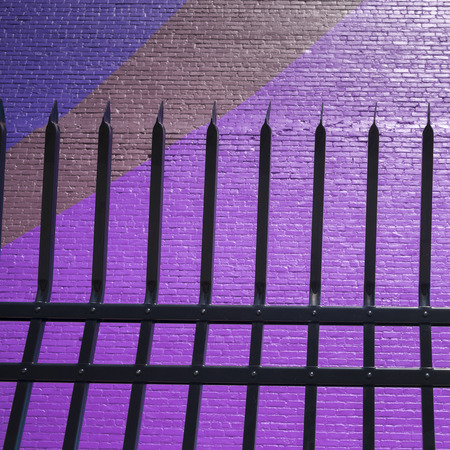 Metal fence by colorful wall, Minneapolis, Hennepin County, Minnesota, USA Stock Photo