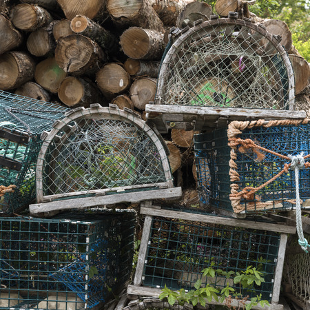 Crab pots stacked by woodpile, Moser River, Marine Drive, Nova Scotia, Canada Stock Photo