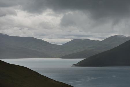 Yamdrok Lake with mountains under cloudy sky, Nagarze, Shannan, Tibet, China
