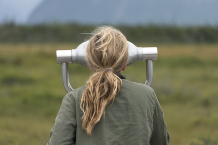 Girl looking through a coin-operated binoculars, Western Brook Pond, Norris Point, Gros Morne National Park, Newfoundland And Labrador, Canada