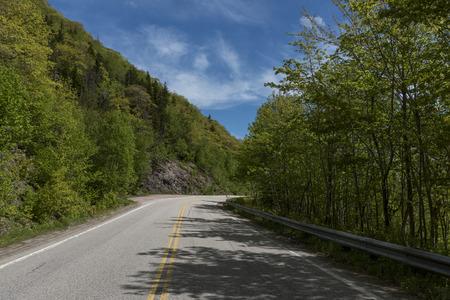 Empty road amidst trees by hills, Dingwall, Cabot Trail, Cape Breton Highlands National Park, Cape Breton Island, Nova Scotia, Canada