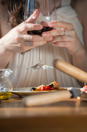 Beautiful young woman eating homemade pizza and drinking red wine at home Stock Photo