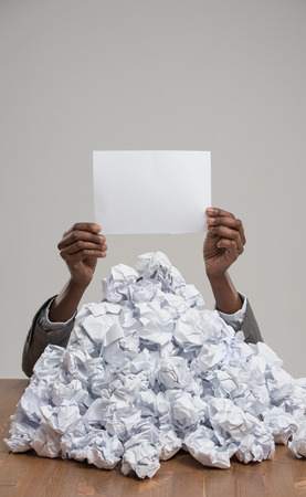 African business woman under crumpled pile of papers with raised hand holding a blank sign