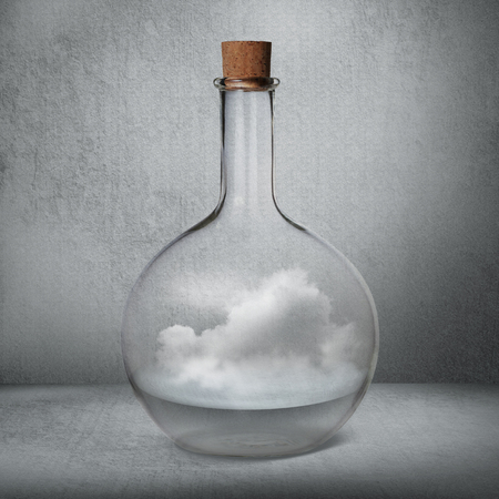Glass bottle with liquid and vapor standing inside gray box Archivio Fotografico