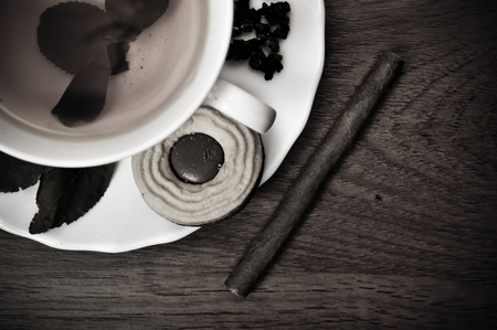 Cup of fresh tea with cigar and cookie on wooden table. Traditional english luxury breakfast. Retro style photo Stock fotó