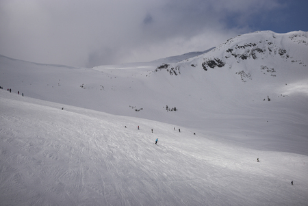 Tourists snowboarding and skiing on snow covered mountain, Whistler, British Columbia, Canada 版權商用圖片