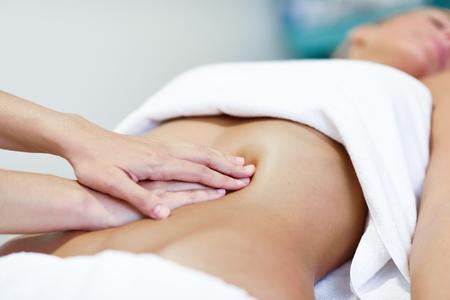 Hands massaging female abdomen.Therapist applying pressure on belly. Woman receiving massage at spa salon Stock Photo