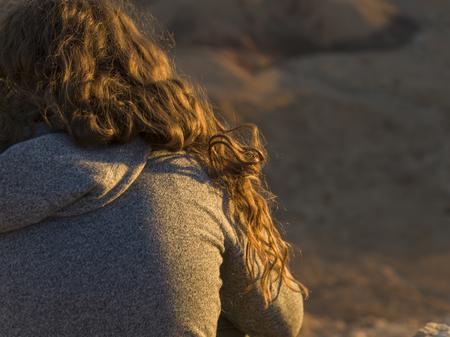 Close-up of teenage girl sitting on rock, Makhtesh Ramon, Negev Desert, Israel