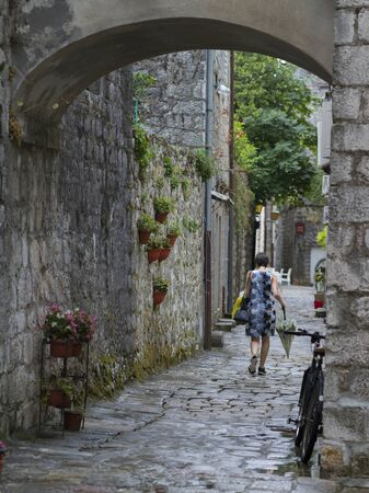 Woman walking in an alley, Perast, Bay of Kotor, Montenegro Stock Photo