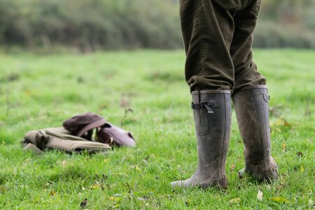 Game shooter stood in a field in his wellington boots