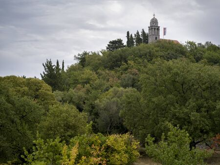 Low angle view of hilltop church surrounded with trees, Karce, Trivet, Montenegro Reklamní fotografie