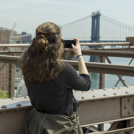 Woman taking a picture on Brooklyn Bridge, Manhattan, New York City, New York State, USA Stock Photo