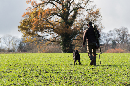Autumnal game shooter with his black labrador peg dog Stok Fotoğraf