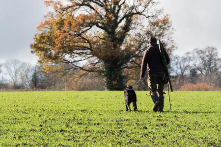 Herbstlicher Game-Shooter mit seinem schwarzen Labrador-Peg Dog