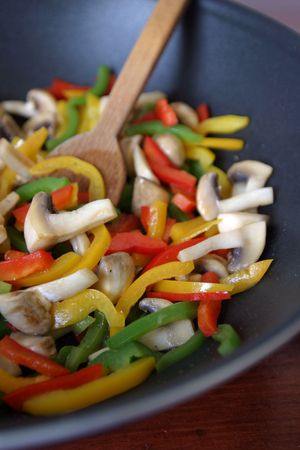 stir fry: Wok with fried colored bell peppers and mushrooms